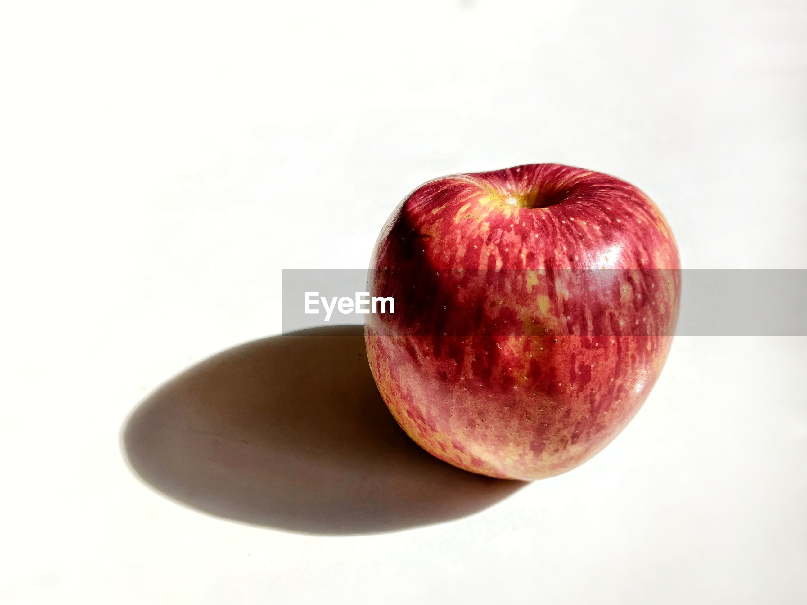 HIGH ANGLE VIEW OF APPLE ON WHITE BACKGROUND