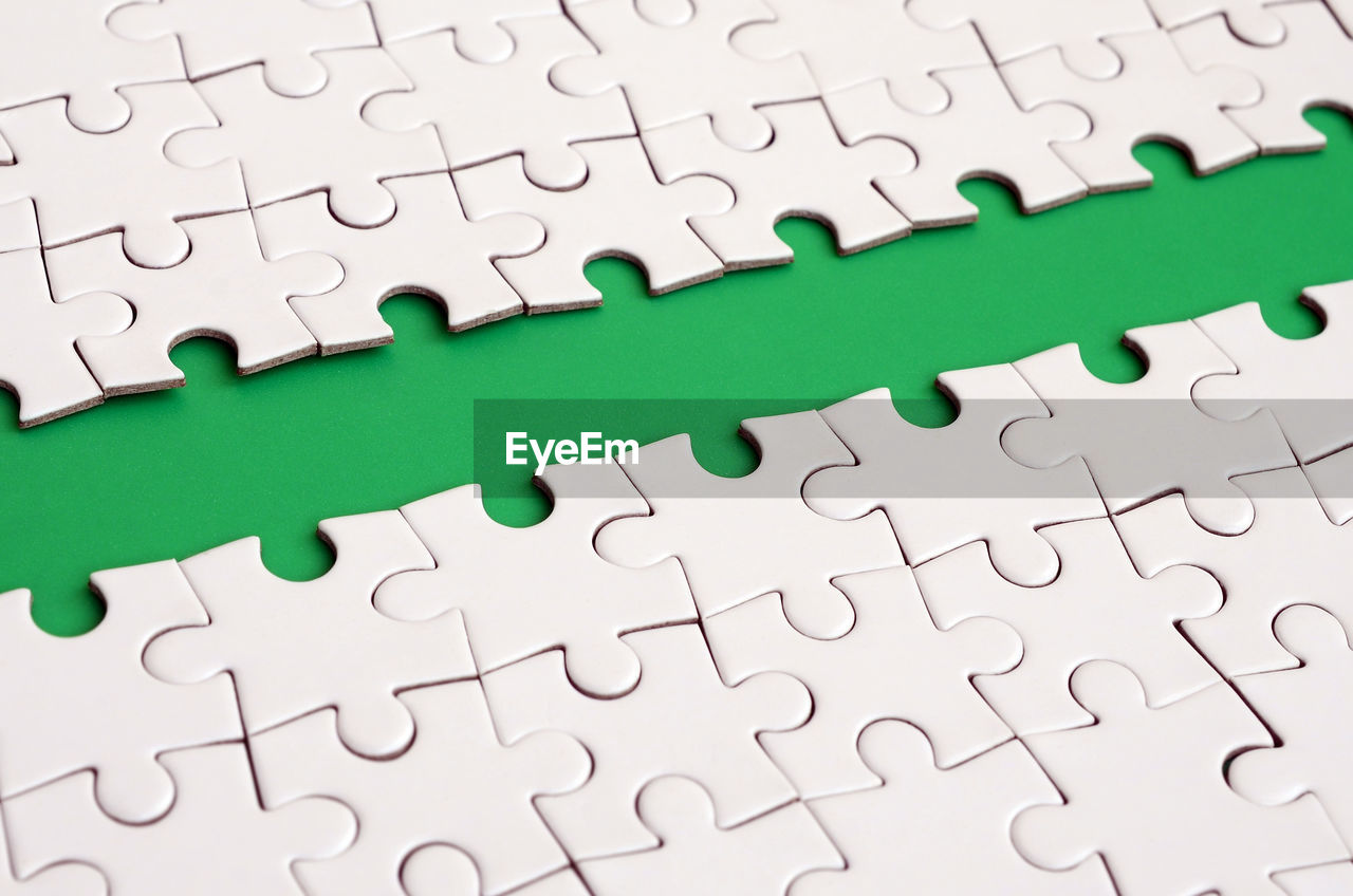 puzzle, jigsaw piece, jigsaw puzzle, solution, pattern, backgrounds, full frame, indoors, green color, no people, connection, leisure activity, leisure games, white color, close-up, incomplete, large group of objects, relaxation, design, high angle view, complexity, blank