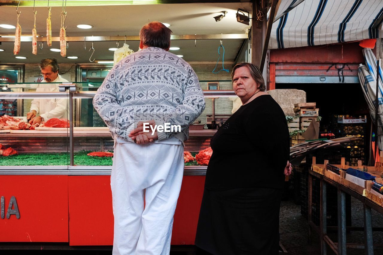 REAR VIEW OF PEOPLE STANDING AT MARKET STALL
