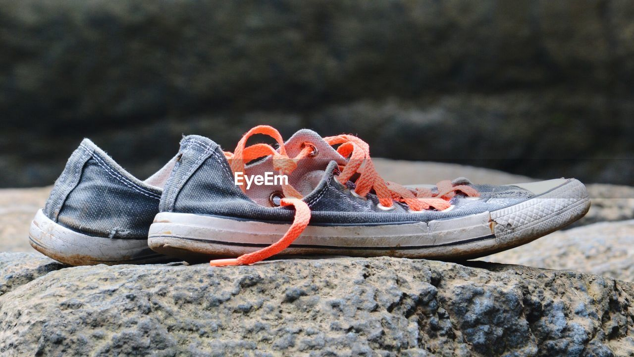 Close-up of shoes on rock