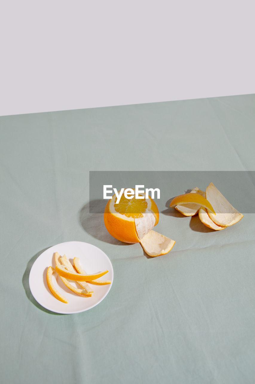 HIGH ANGLE VIEW OF ORANGE SLICE ON TABLE