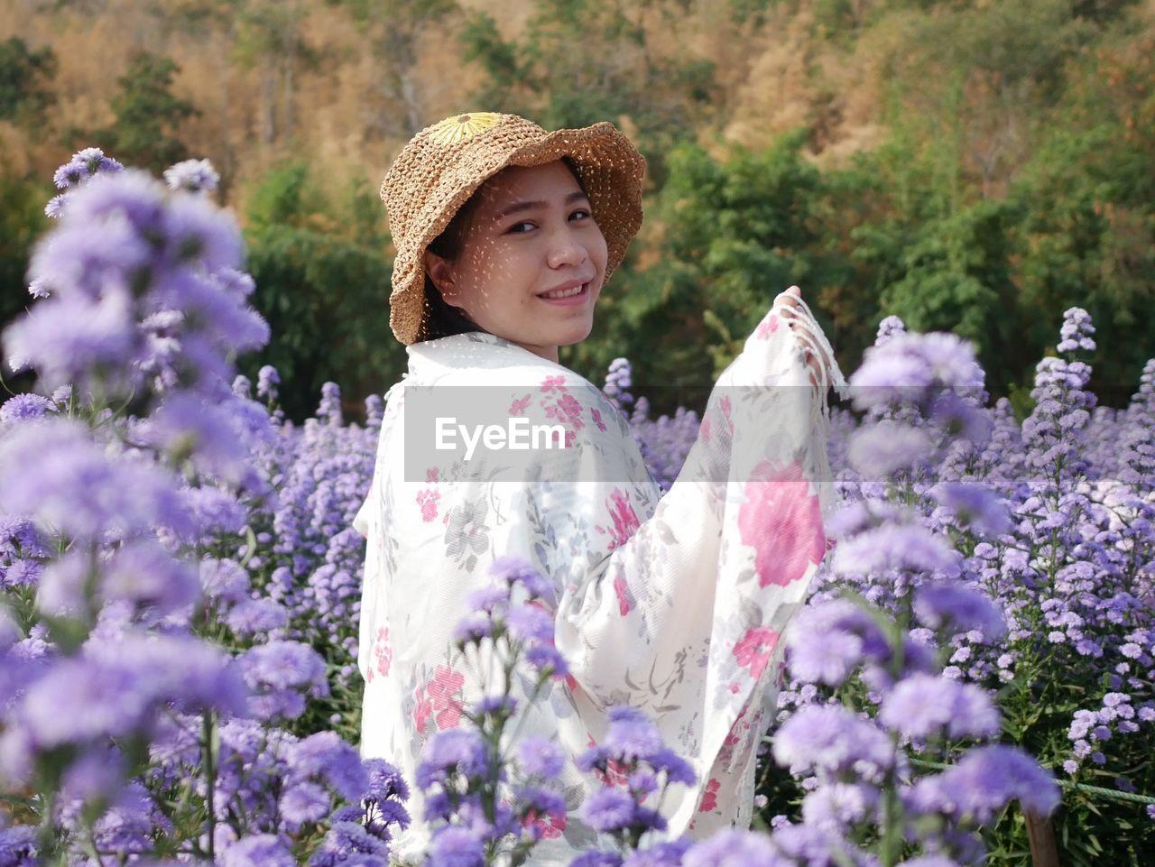 WOMAN STANDING ON PURPLE FLOWERING PLANT