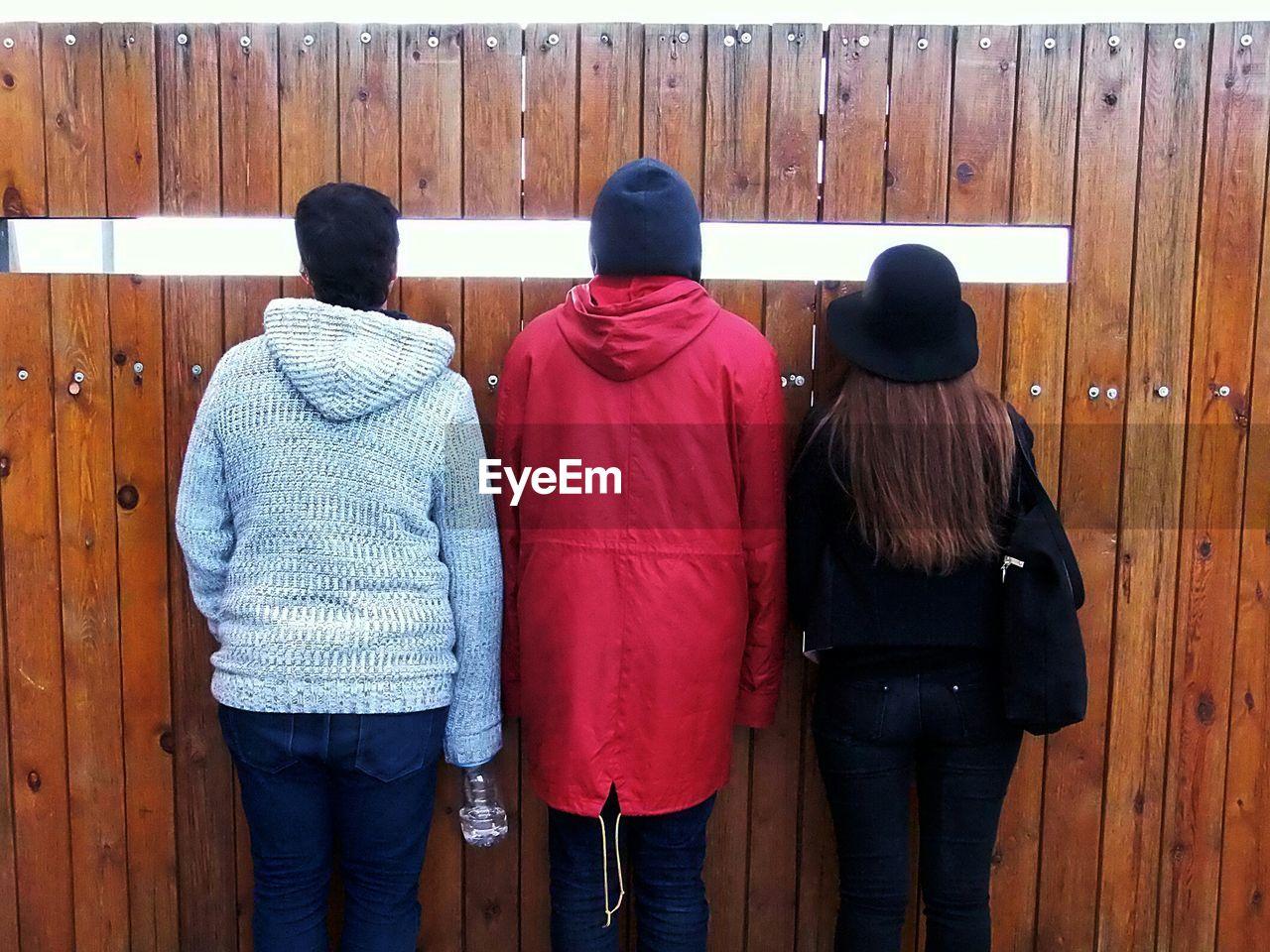 Rear View Of Friends Peeking Through Wooden Fence