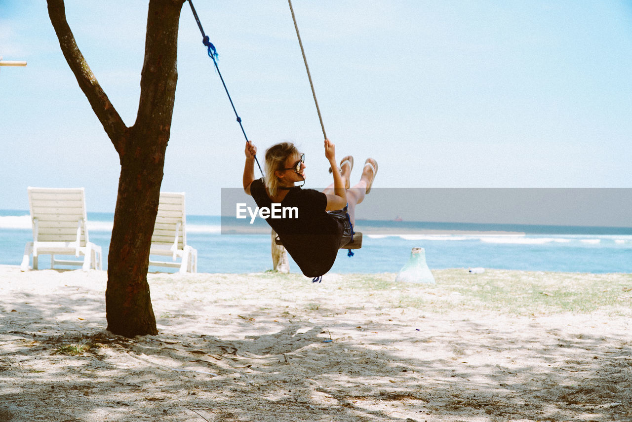 Rear View Of Woman On Swing At Beach
