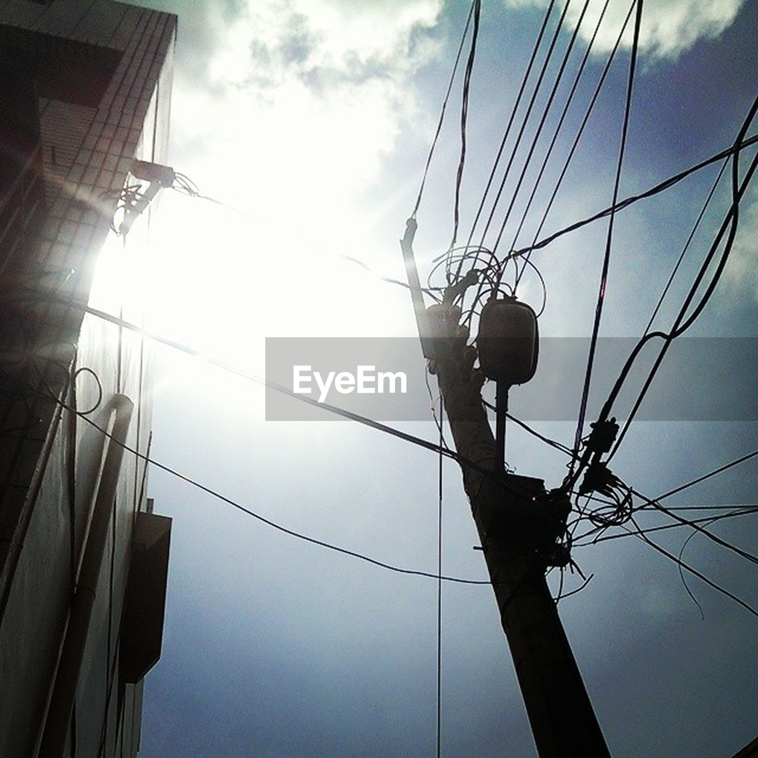 low angle view, electricity, power line, sky, cable, lighting equipment, street light, built structure, architecture, technology, power supply, electricity pylon, connection, building exterior, pole, fuel and power generation, silhouette, communication, power cable, cloud - sky
