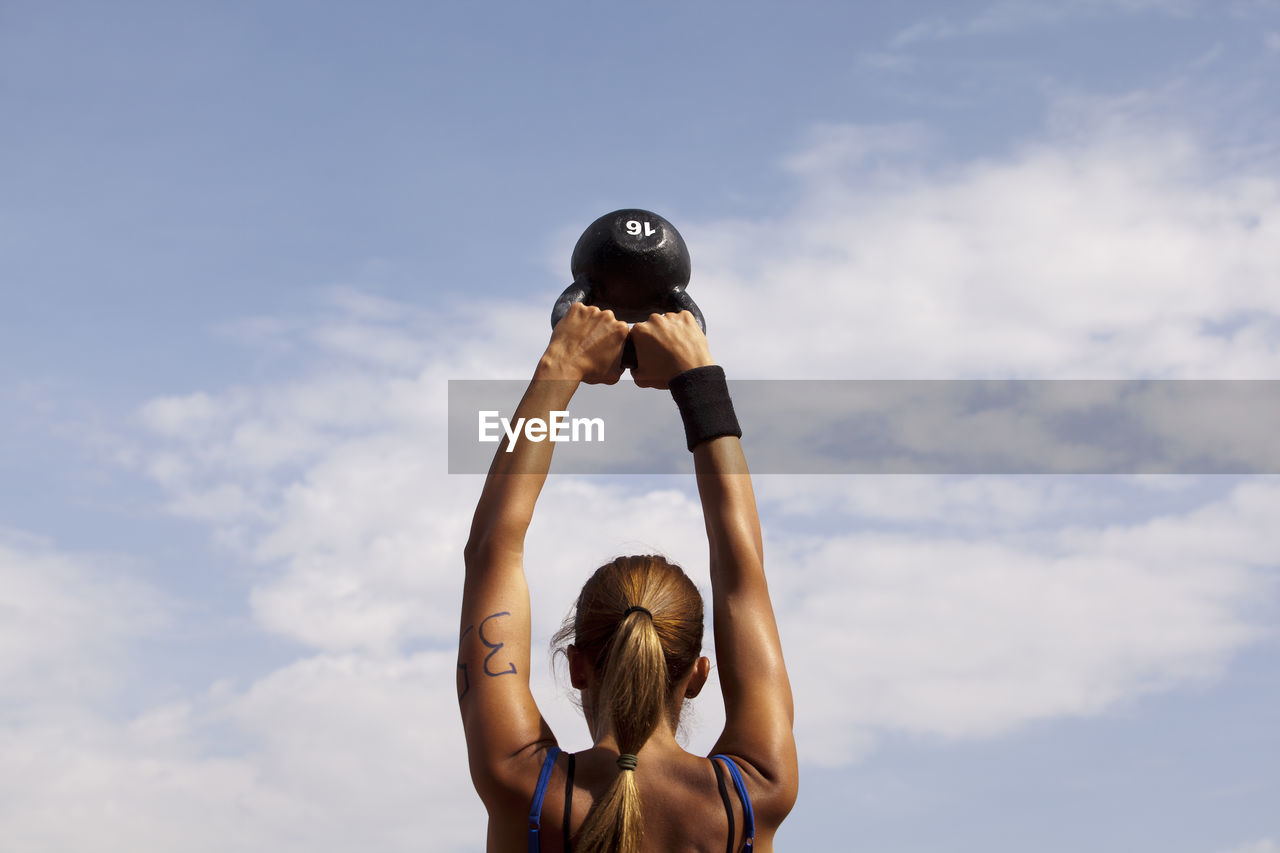 low angle view, cloud - sky, sky, real people, arms raised, leisure activity, one person, lifestyles, rear view, sport, exercising, day, healthy lifestyle, outdoors, women, headshot, childhood, sports clothing, adult, people