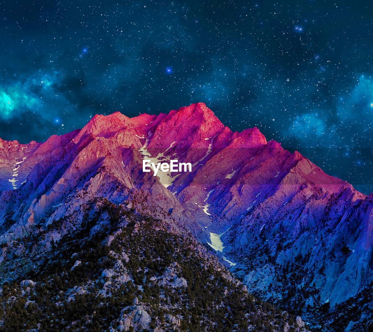 Low angle view of mountain range against starry sky