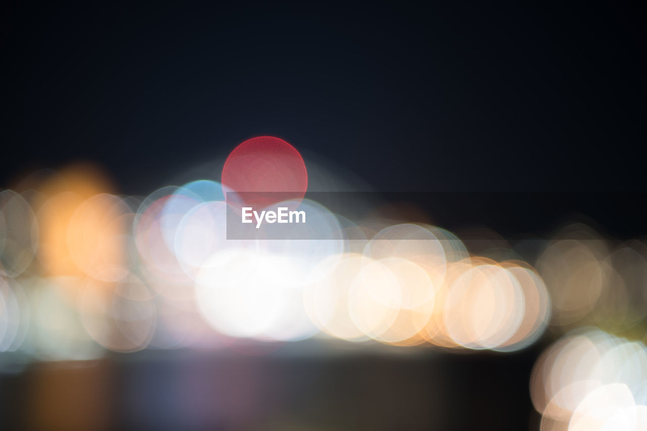 illuminated, night, lens flare, defocused, light effect, glowing, no people, outdoors, focus on foreground, close-up, sky