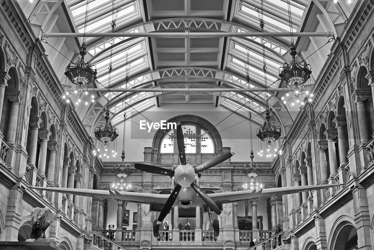 architecture, ceiling, indoors, built structure, public transportation, hanging, low angle view, travel, no people, transportation, museum, rail transportation, day, representation, skylight, pattern, mode of transportation, metal, arch, travel destinations