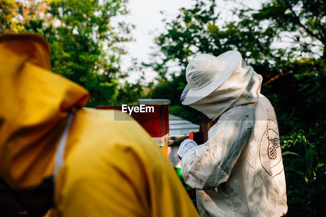 Beekeepers Standing By Beehive