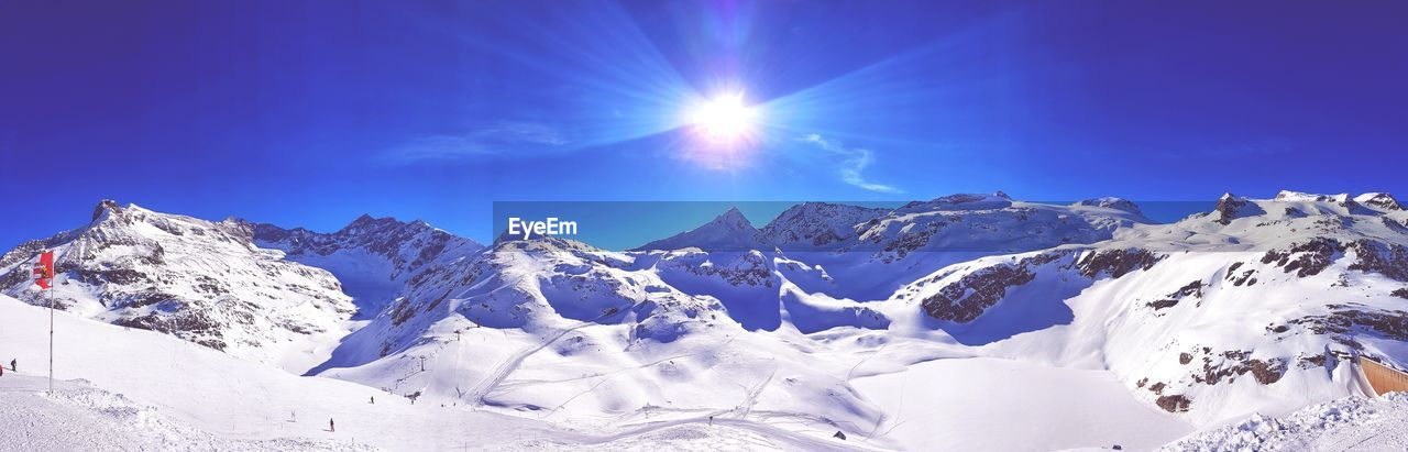 sky, beauty in nature, winter, snow, sunlight, scenics - nature, cold temperature, mountain, tranquil scene, sun, tranquility, nature, blue, lens flare, sunbeam, snowcapped mountain, day, sunny, idyllic, mountain range, bright, no people, mountain peak