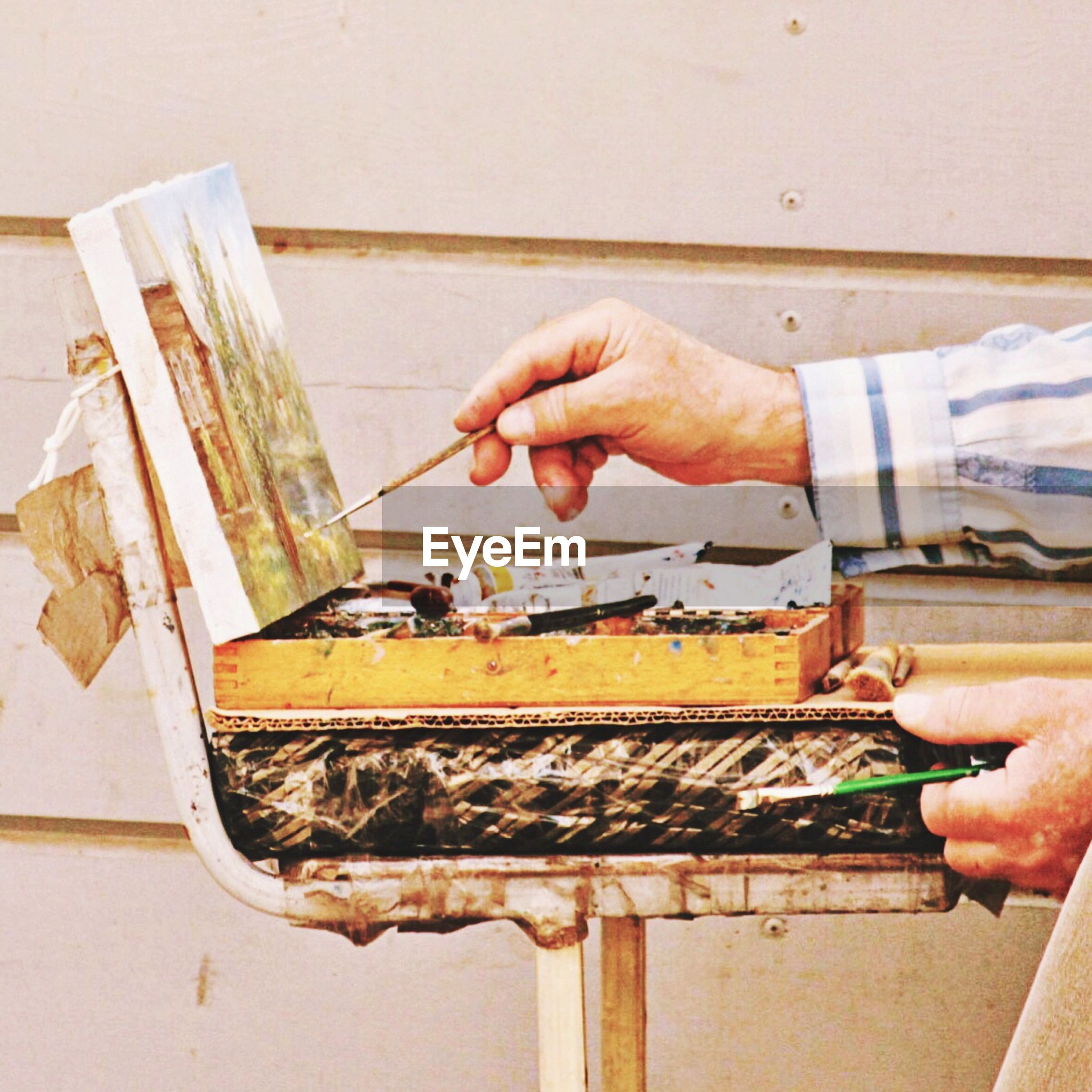 Cropped image of painter painting against wall