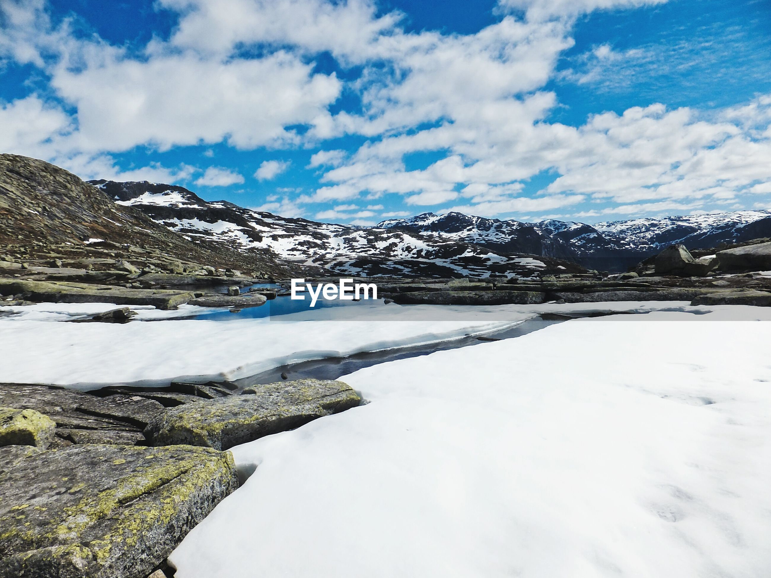 Scenic view of lake and snow covered field by mountains against sky