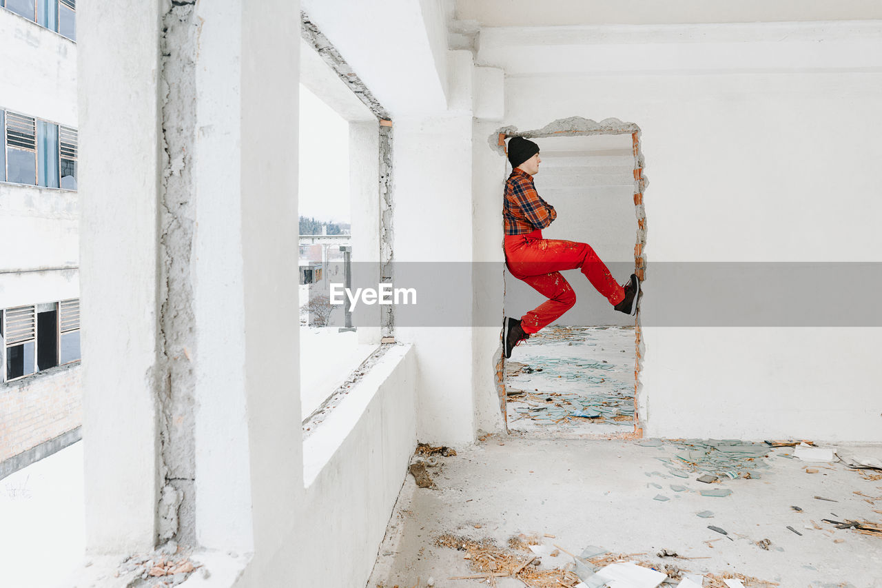 Side View Of Man Climbing At Doorway In Abandoned Building