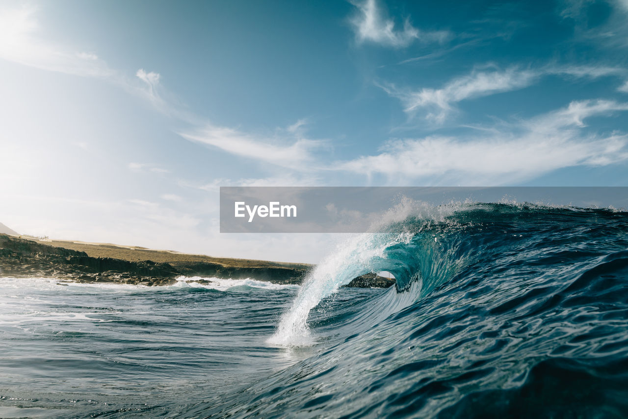 Scenic view of waves in sea against sky