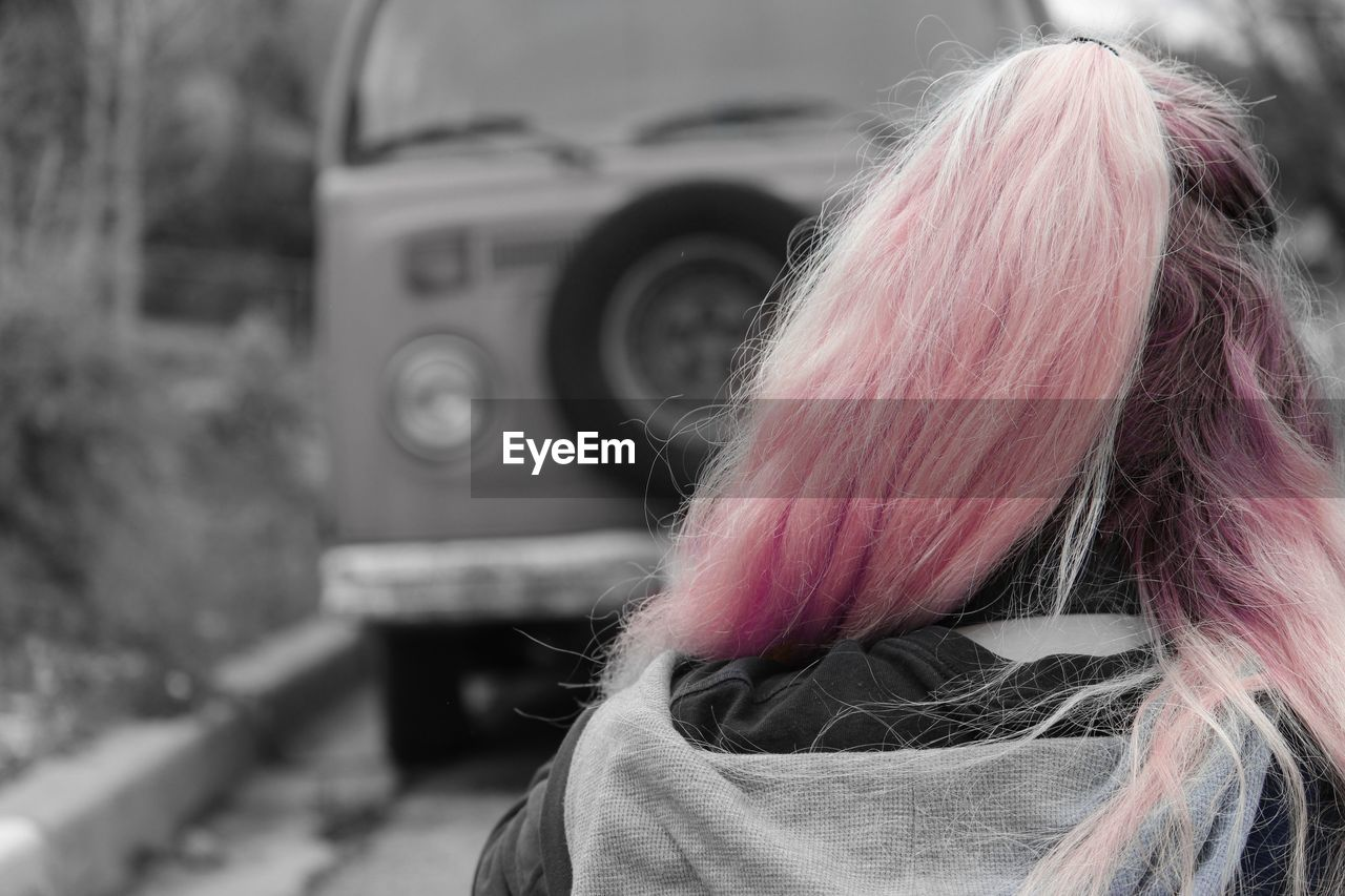 human hair, focus on foreground, real people, rear view, leisure activity, one person, fashion, close-up, pink hair, lifestyles, outdoors, day, technology, human hand, people