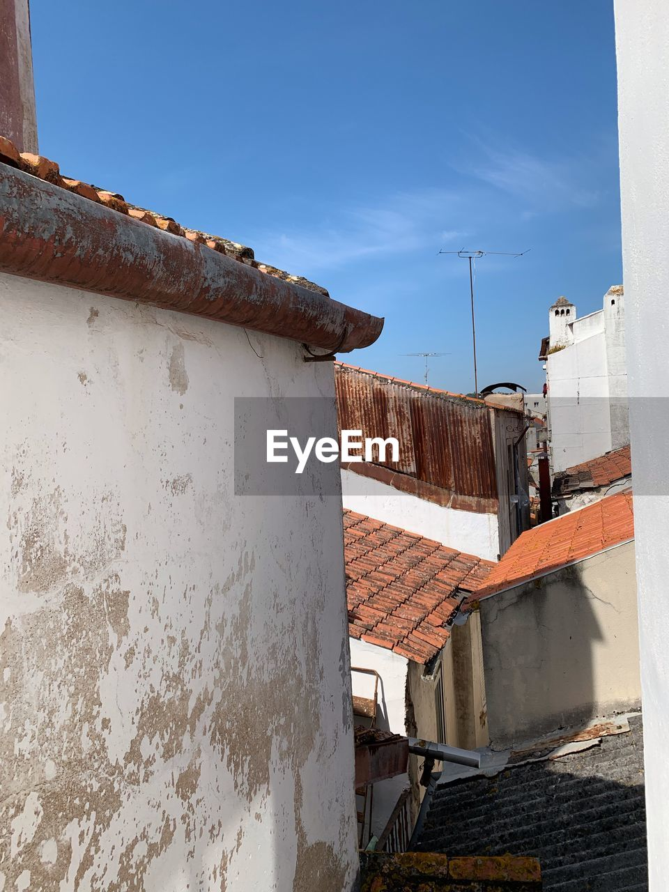architecture, built structure, building exterior, sky, building, nature, day, blue, no people, residential district, house, roof, clear sky, sunlight, old, outdoors, low angle view, window, metal, rusty, roof tile