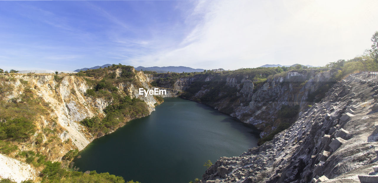 PANORAMIC SHOT OF RIVER AMIDST MOUNTAINS AGAINST SKY