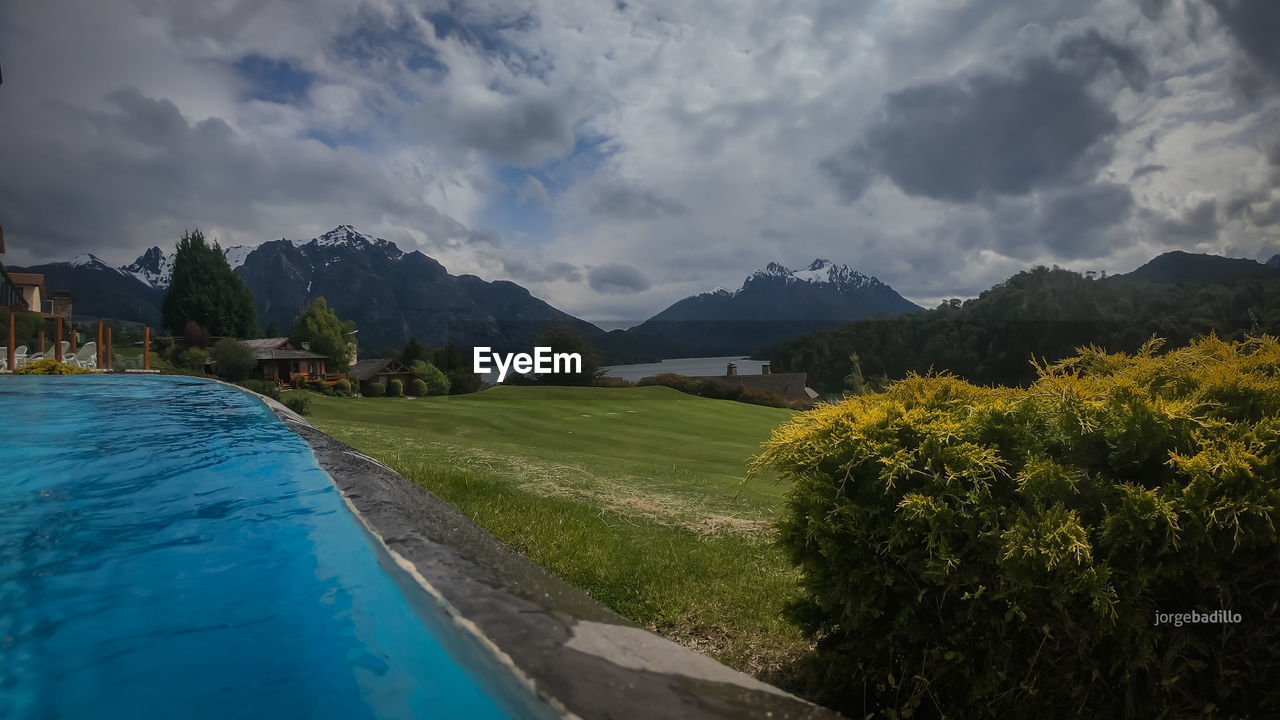 cloud - sky, sky, plant, mountain, nature, scenics - nature, beauty in nature, water, tranquility, tree, no people, tranquil scene, swimming pool, day, architecture, mountain range, green color, idyllic, outdoors