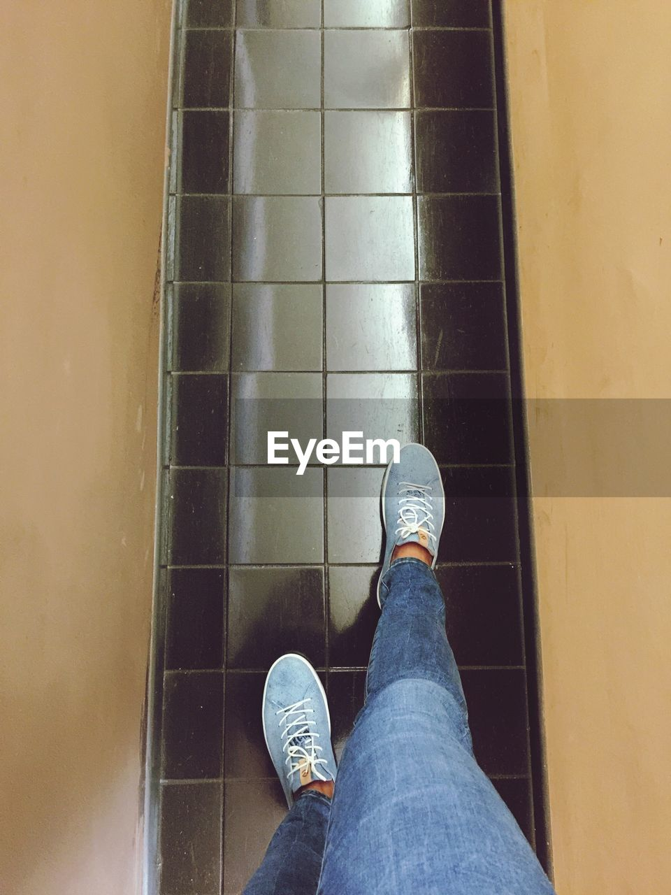 low section, human leg, shoe, body part, human body part, personal perspective, jeans, real people, casual clothing, one person, lifestyles, high angle view, men, standing, tile, architecture, flooring, day, indoors, tiled floor, human foot, human limb