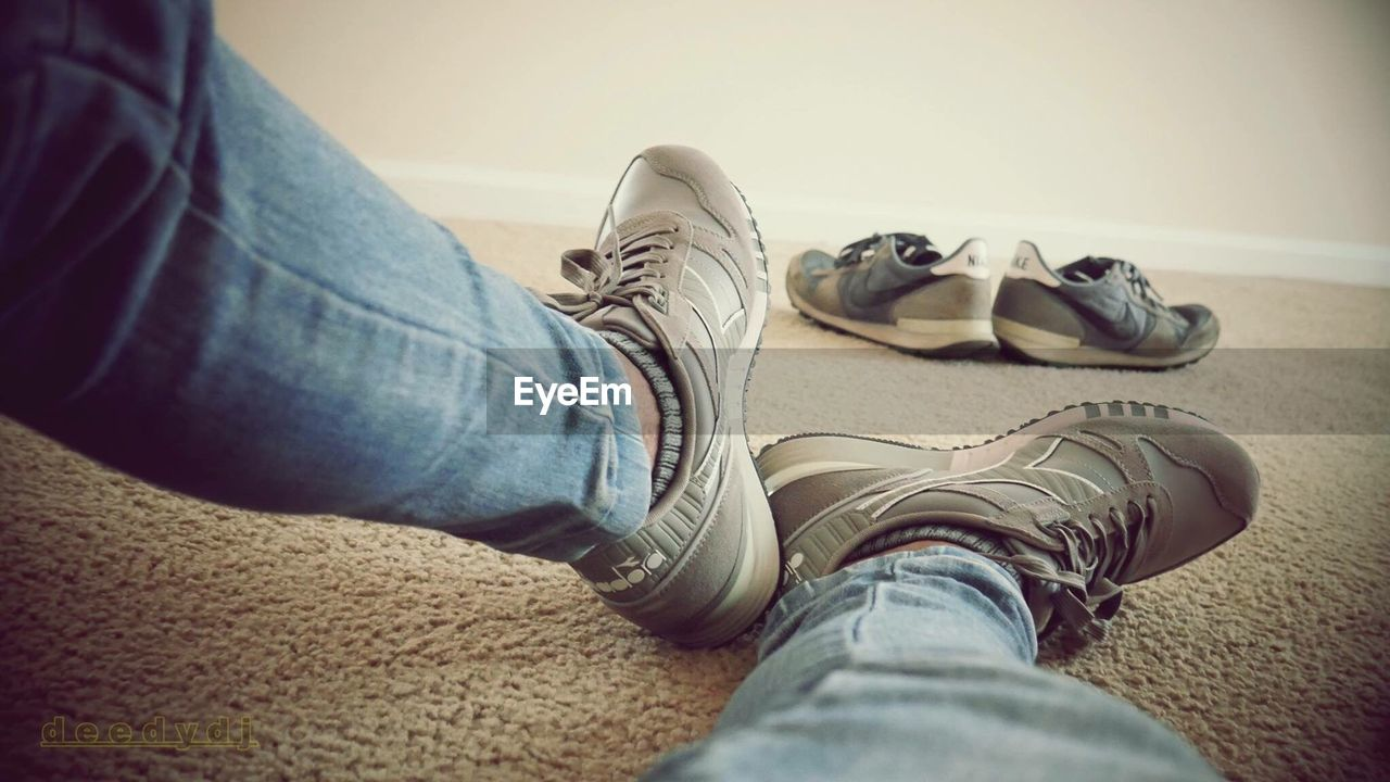 jeans, shoe, low section, human leg, real people, one person, indoors, casual clothing, personal perspective, men, human body part, canvas shoe, lifestyles, sitting, close-up, day, one man only, people, adult