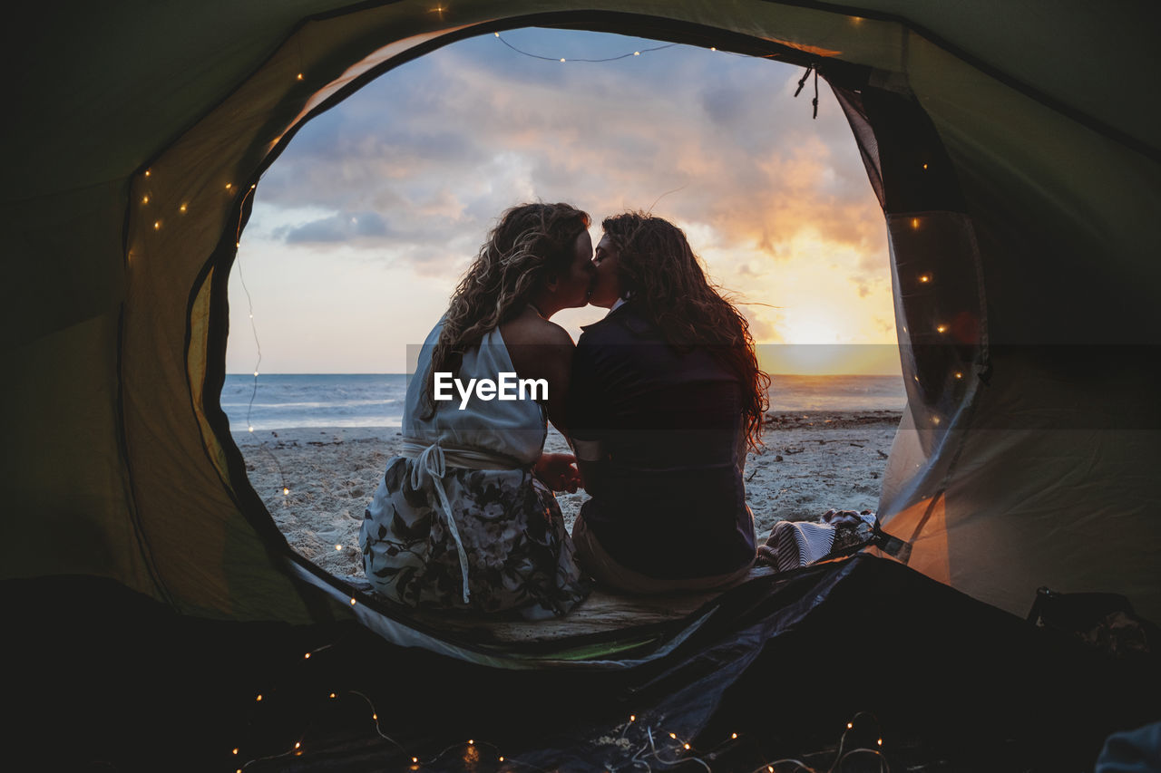 Lesbian Couple Kissing In Tent At Beach During Sunset