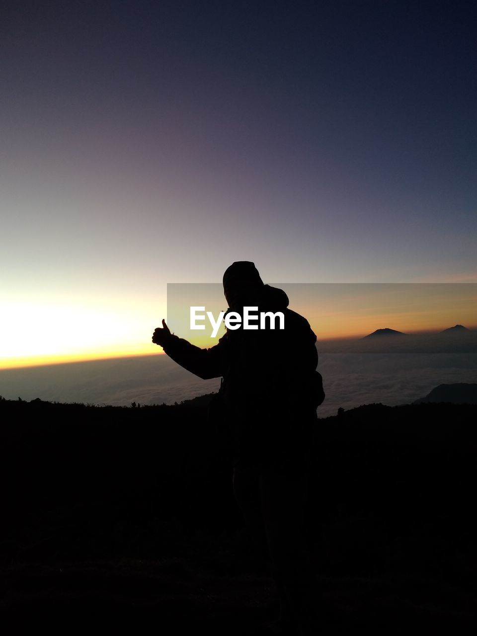SILHOUETTE MAN STANDING ON FIELD AGAINST SKY AT SUNSET