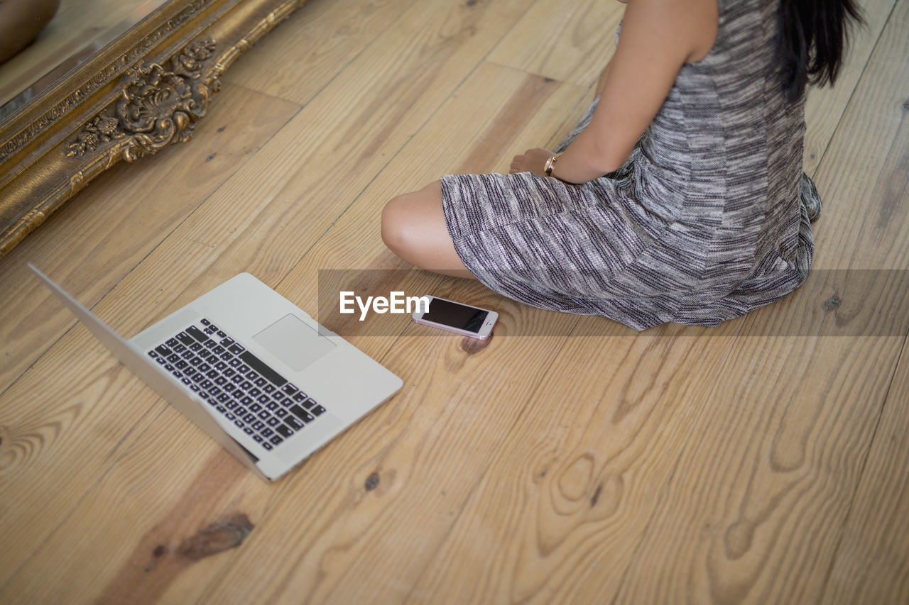 HIGH ANGLE VIEW OF WOMAN USING MOBILE PHONE ON WOODEN TABLE