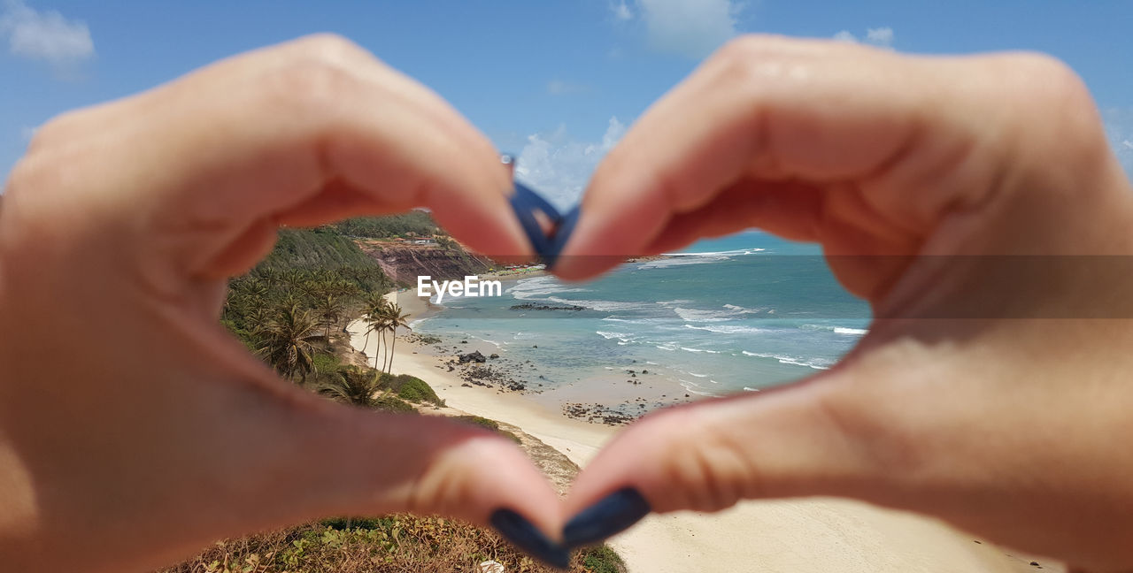 Cropped Image Of Woman Making Heart Shape With Hands Against Beach