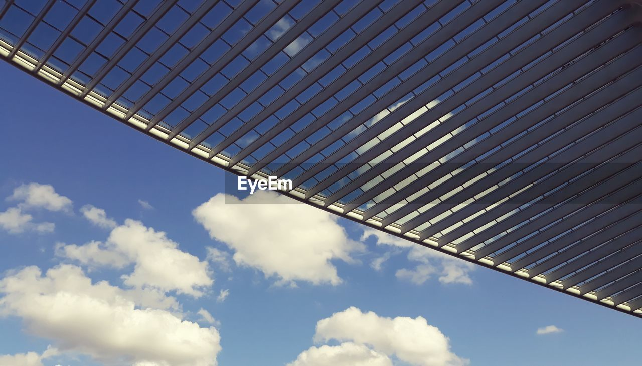 cloud - sky, sky, low angle view, architecture, built structure, no people, nature, day, metal, building exterior, pattern, blue, outdoors, sunlight, connection, building, modern, environmental conservation, bridge, roof