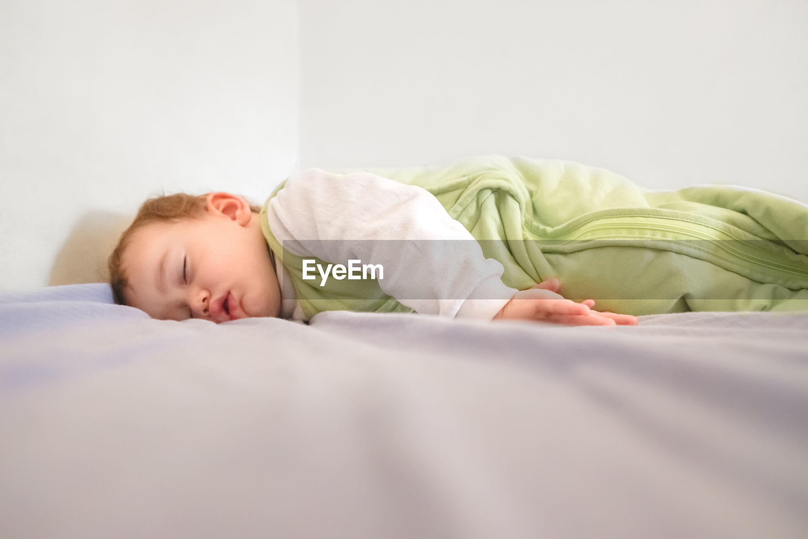 Baby girl sleeping on bed