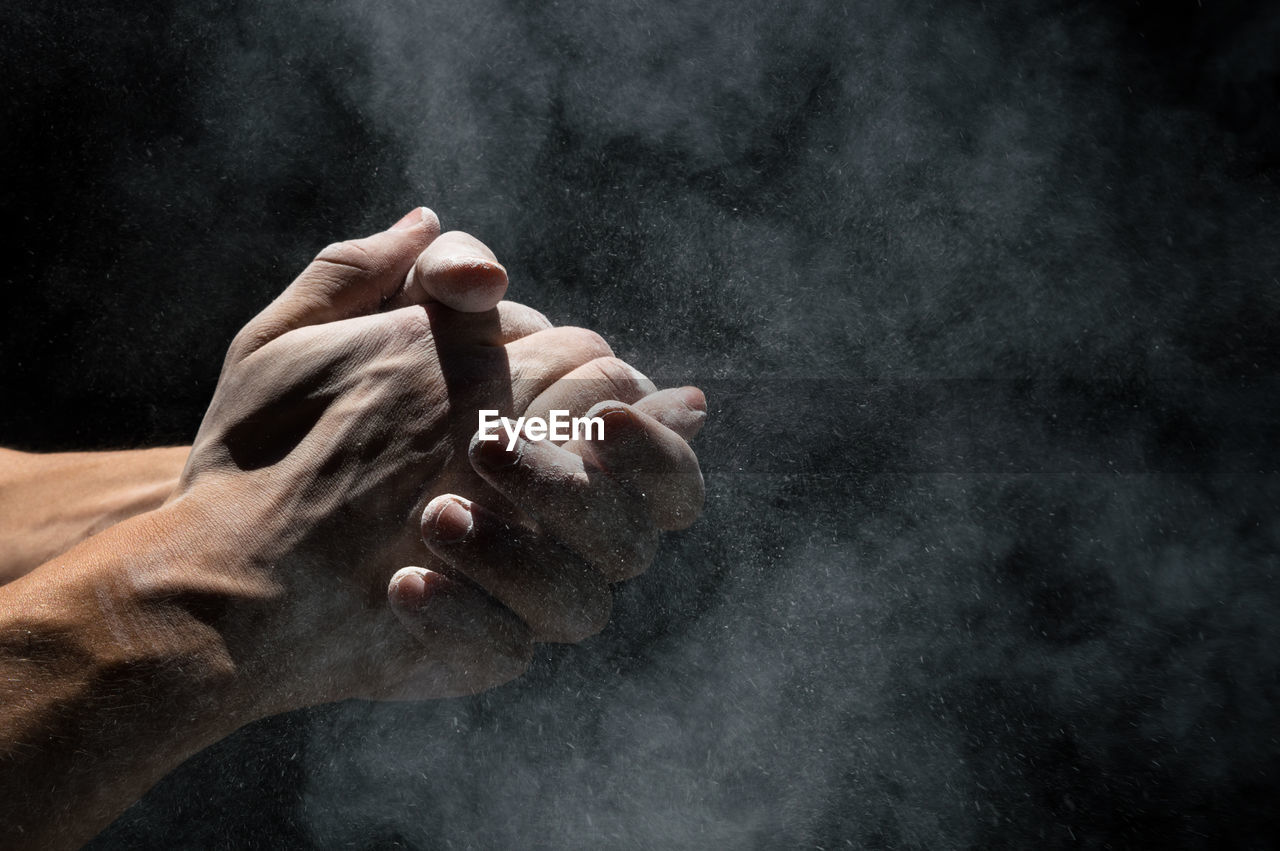 Cropped image of hand with powder against black background