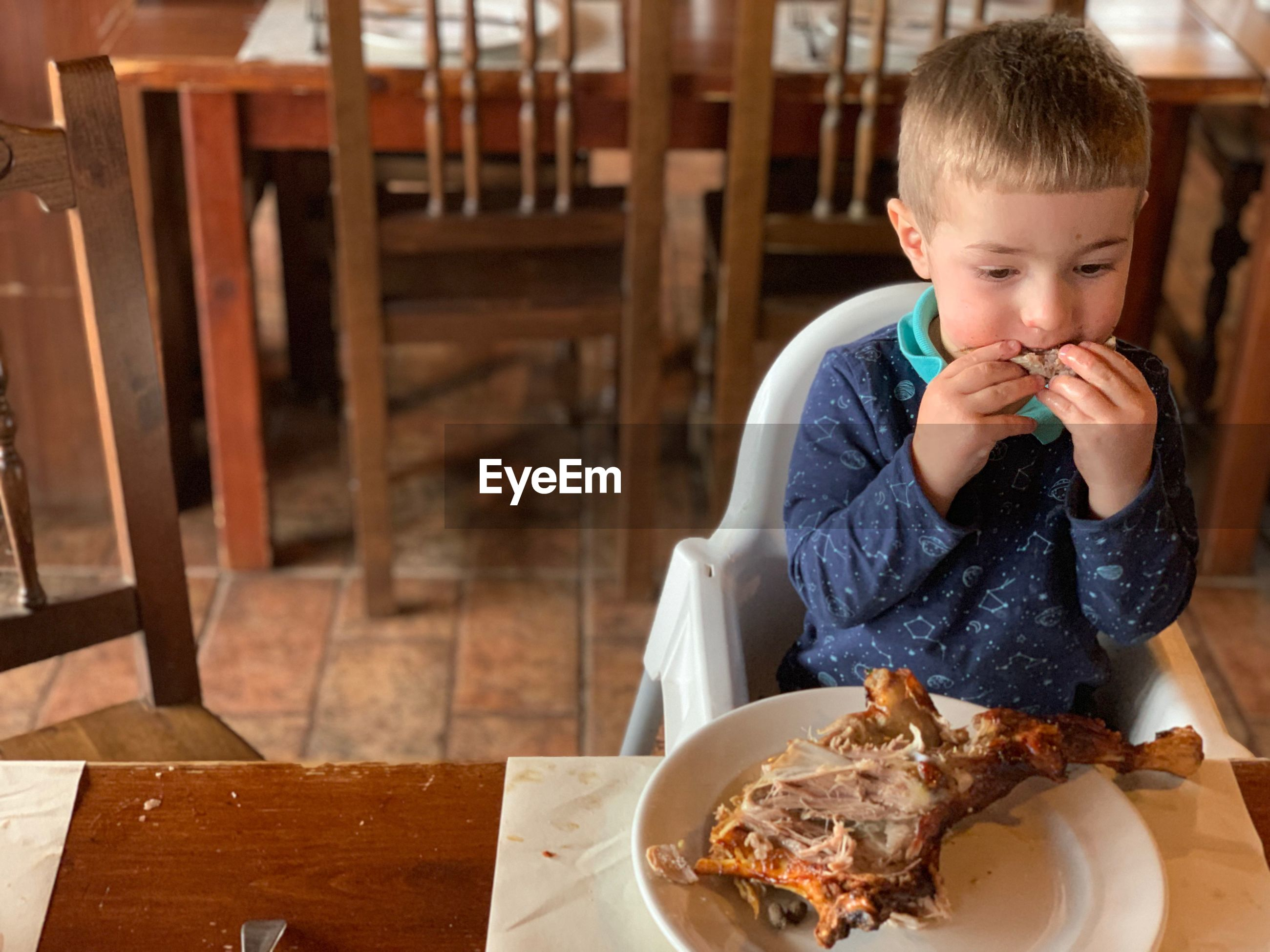 High angle view of boy eating meat while sitting at home