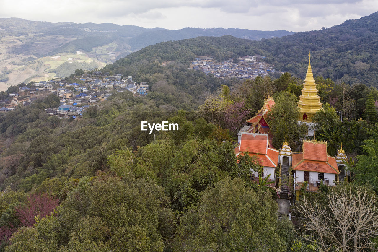PANORAMIC VIEW OF TREES AND BUILDINGS AGAINST MOUNTAIN