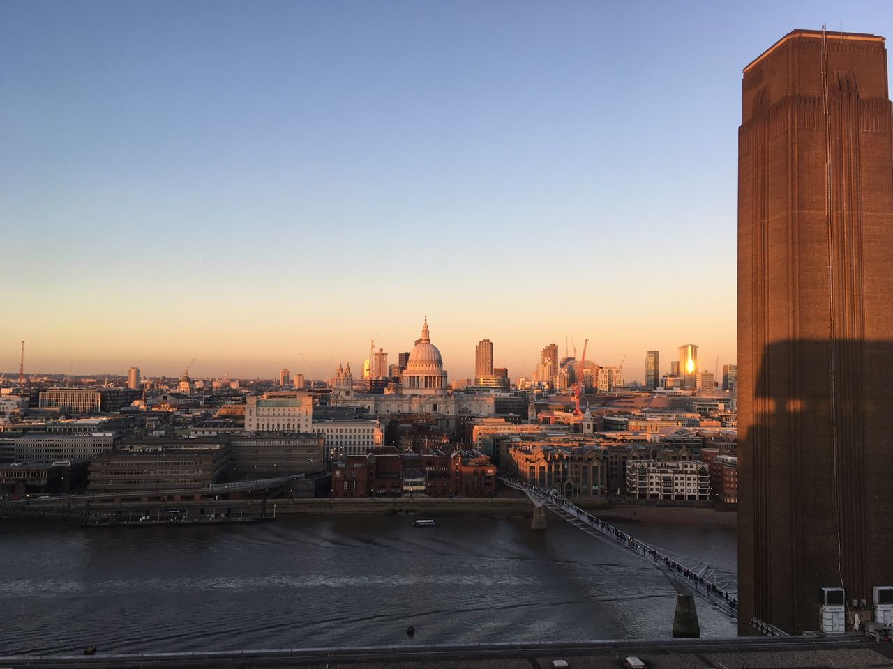 architecture, built structure, building exterior, cityscape, city, sunset, travel destinations, river, religion, outdoors, skyscraper, place of worship, spirituality, urban skyline, travel, clear sky, sky, no people, water, day