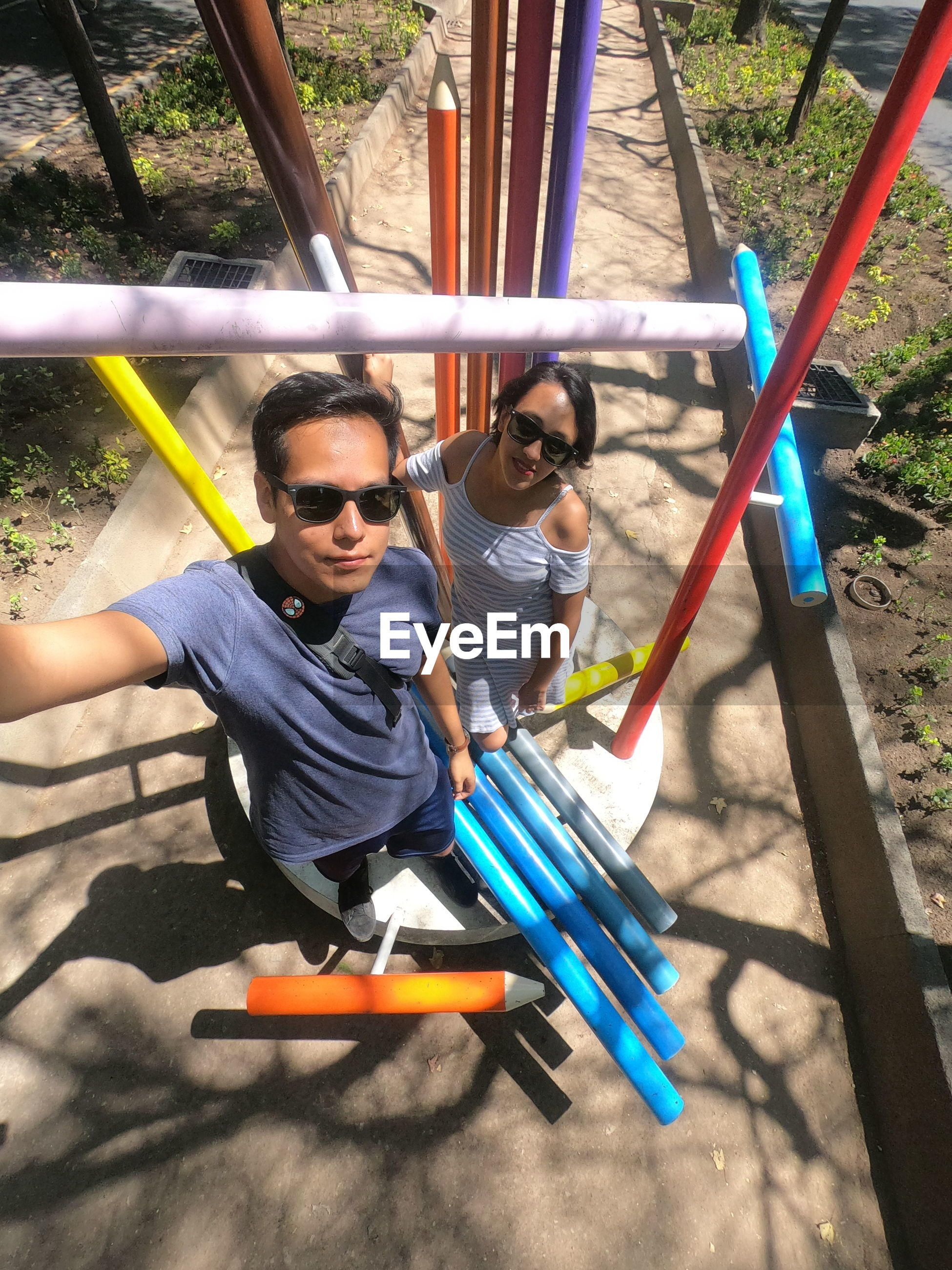 High angle portrait of friends wearing sunglasses while standing at playground