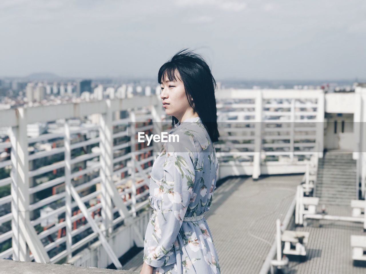 Side View Of Young Woman Standing Against Cityscape
