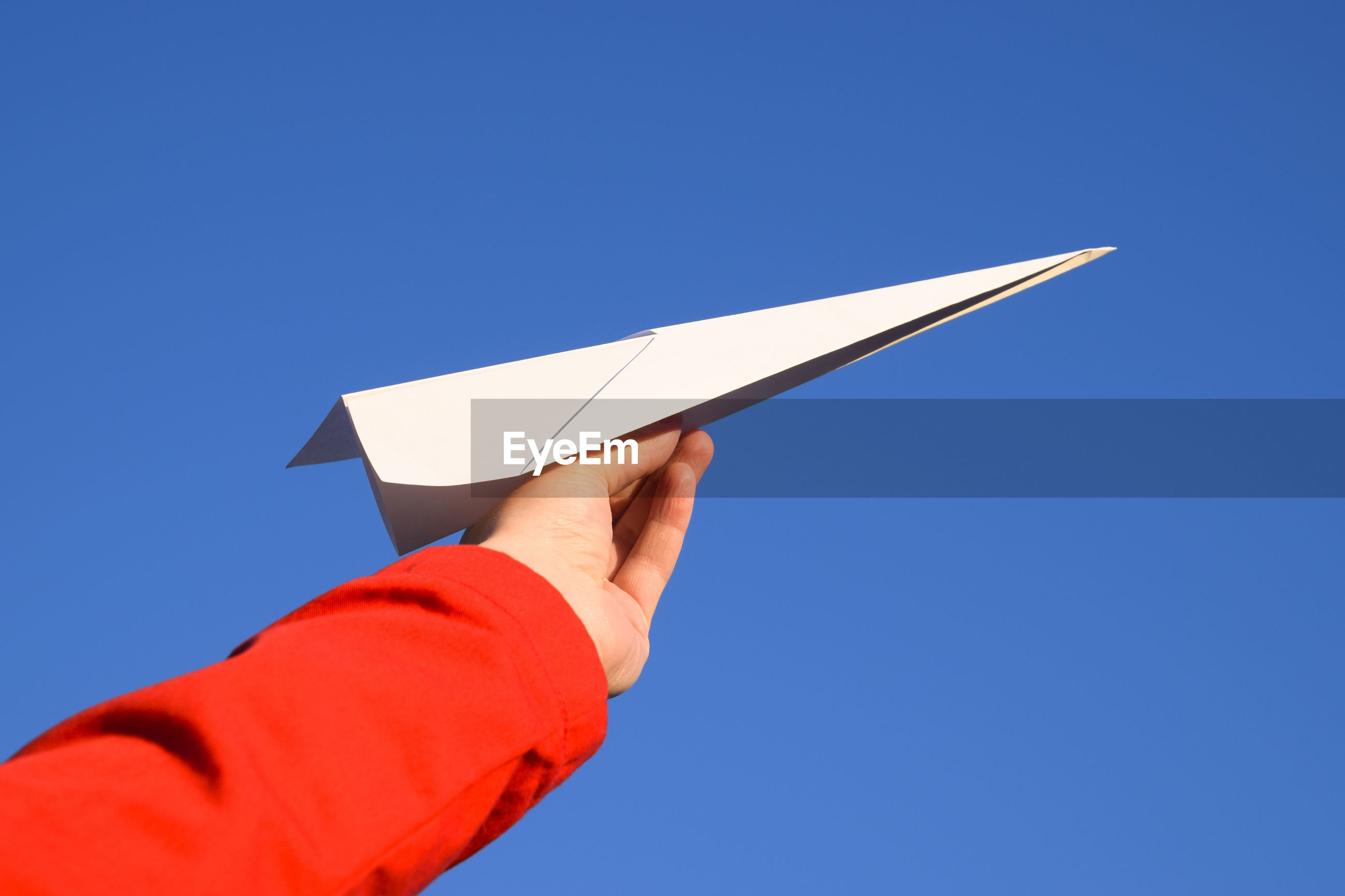 Cropped image of hand holding paper airplane against clear blue sky