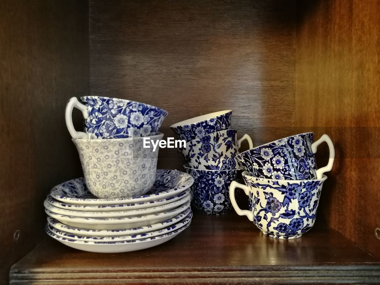 indoors, table, wood - material, cup, ceramics, no people, crockery, still life, close-up, pattern, blue, mug, bowl, porcelain, floral pattern, food and drink, stack, art and craft, saucer, group of objects, ornate, tea cup