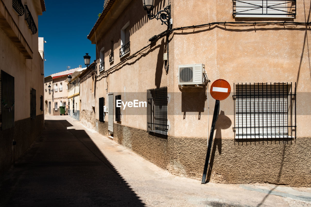 building exterior, built structure, architecture, building, city, residential district, road sign, road, sunlight, street, day, sign, nature, no people, window, shadow, direction, communication, outdoors, sky, alley