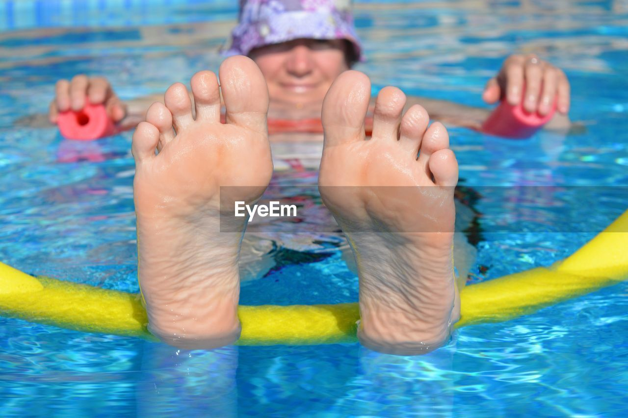 Smiling woman with barefoot swimming in pool