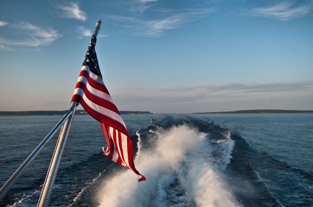 American Flag Against Wake In Sea