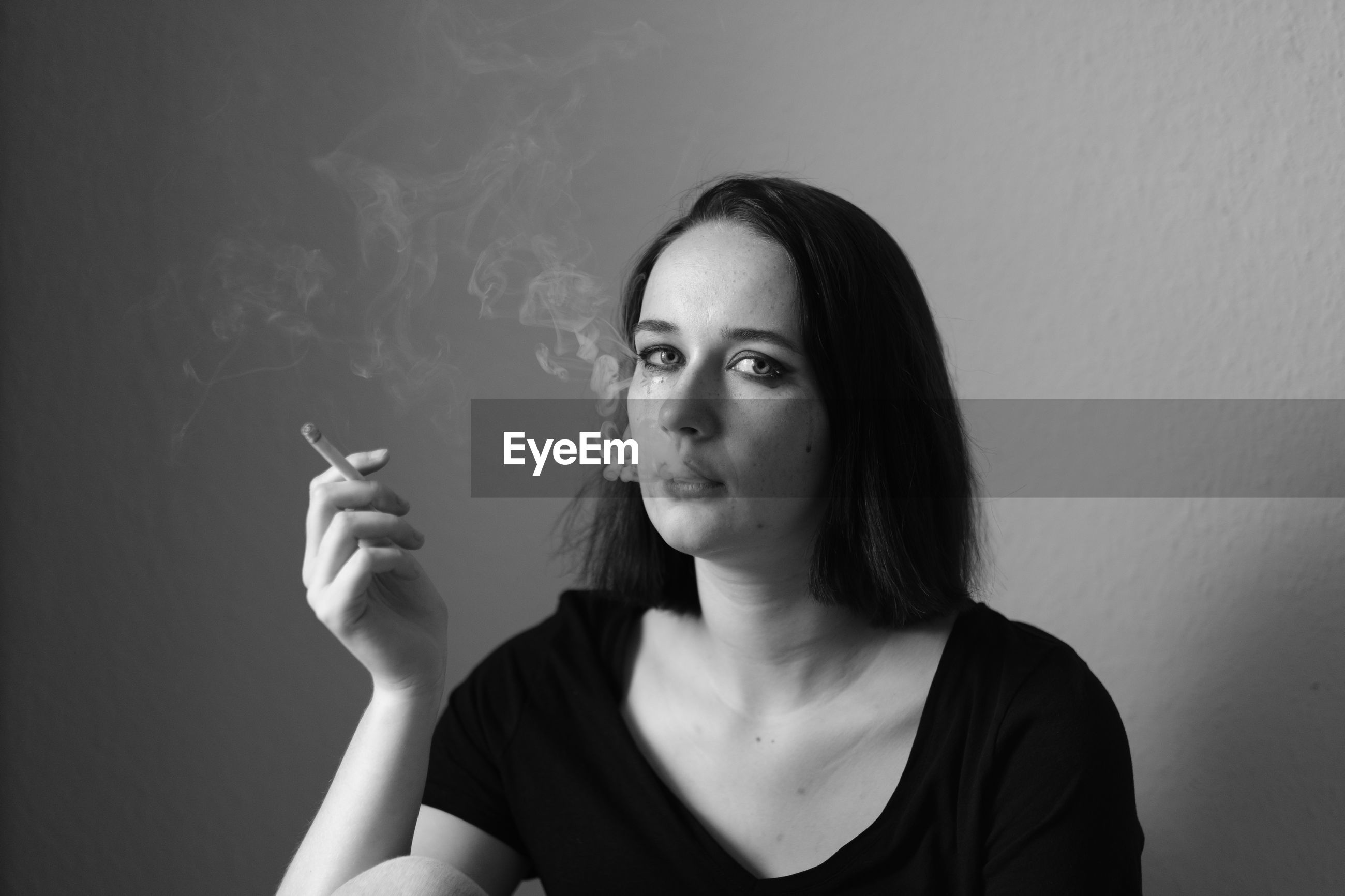 Portrait of young woman with cigarette sitting against wall at home