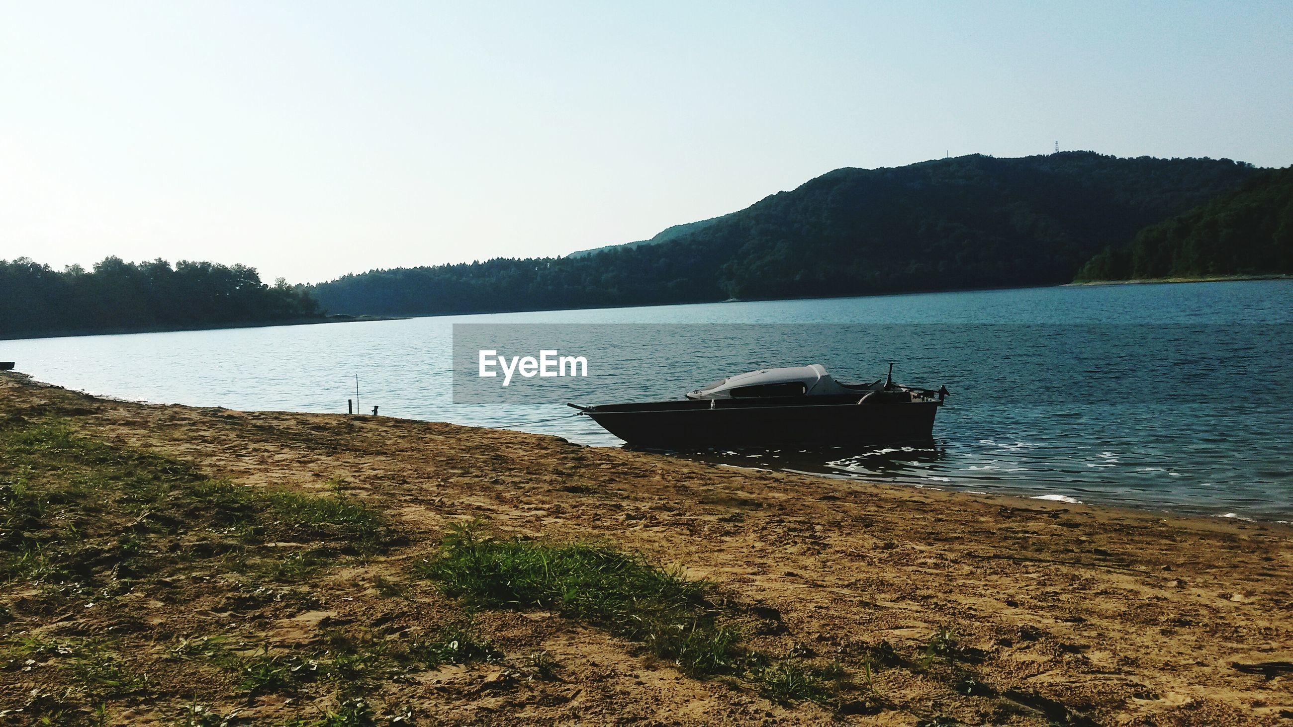 Motorboat moored at shore in lake against sky