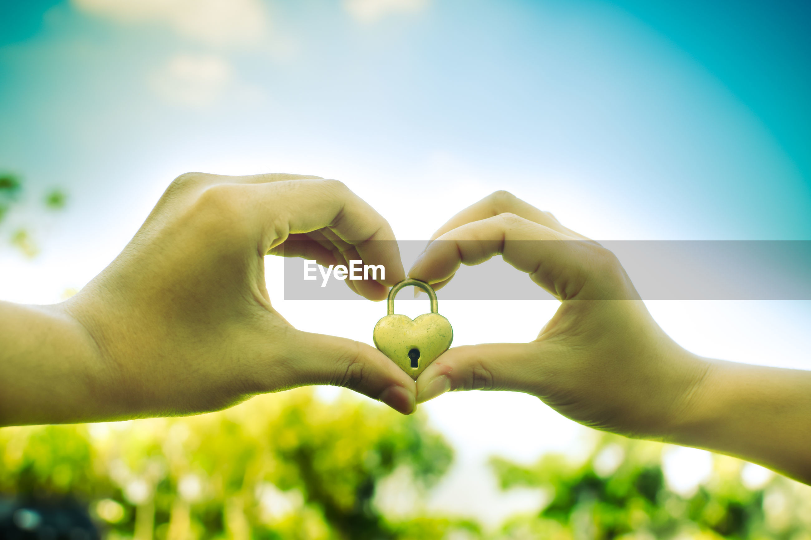 Cropped hands of couple holding love lock against sky