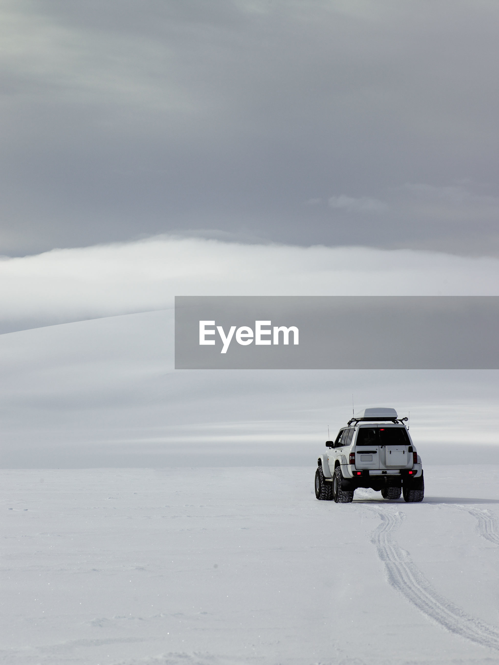 CAR ON SNOW COVERED ROAD AGAINST SKY