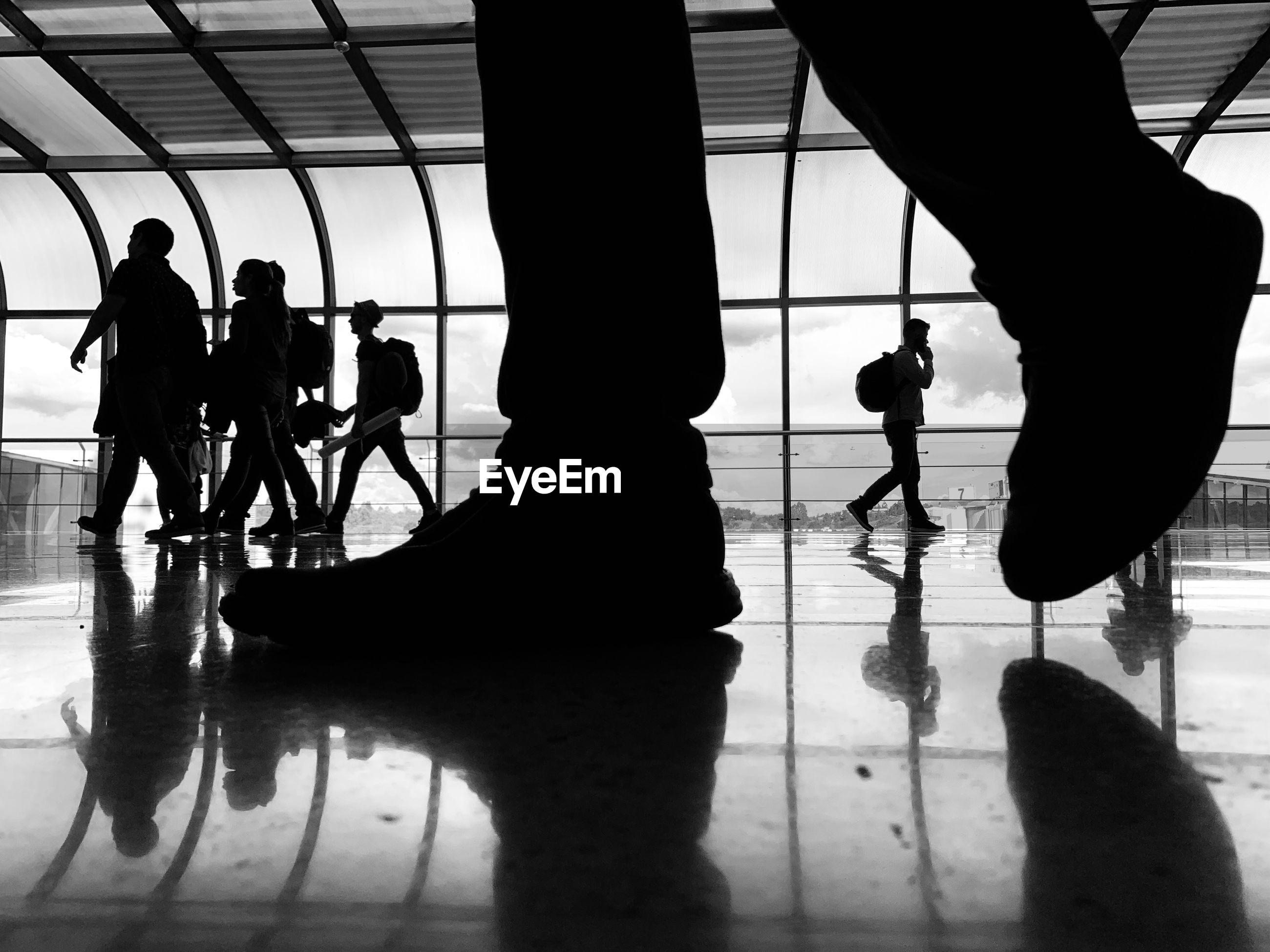 SILHOUETTE PEOPLE WALKING ON AIRPORT FLOOR