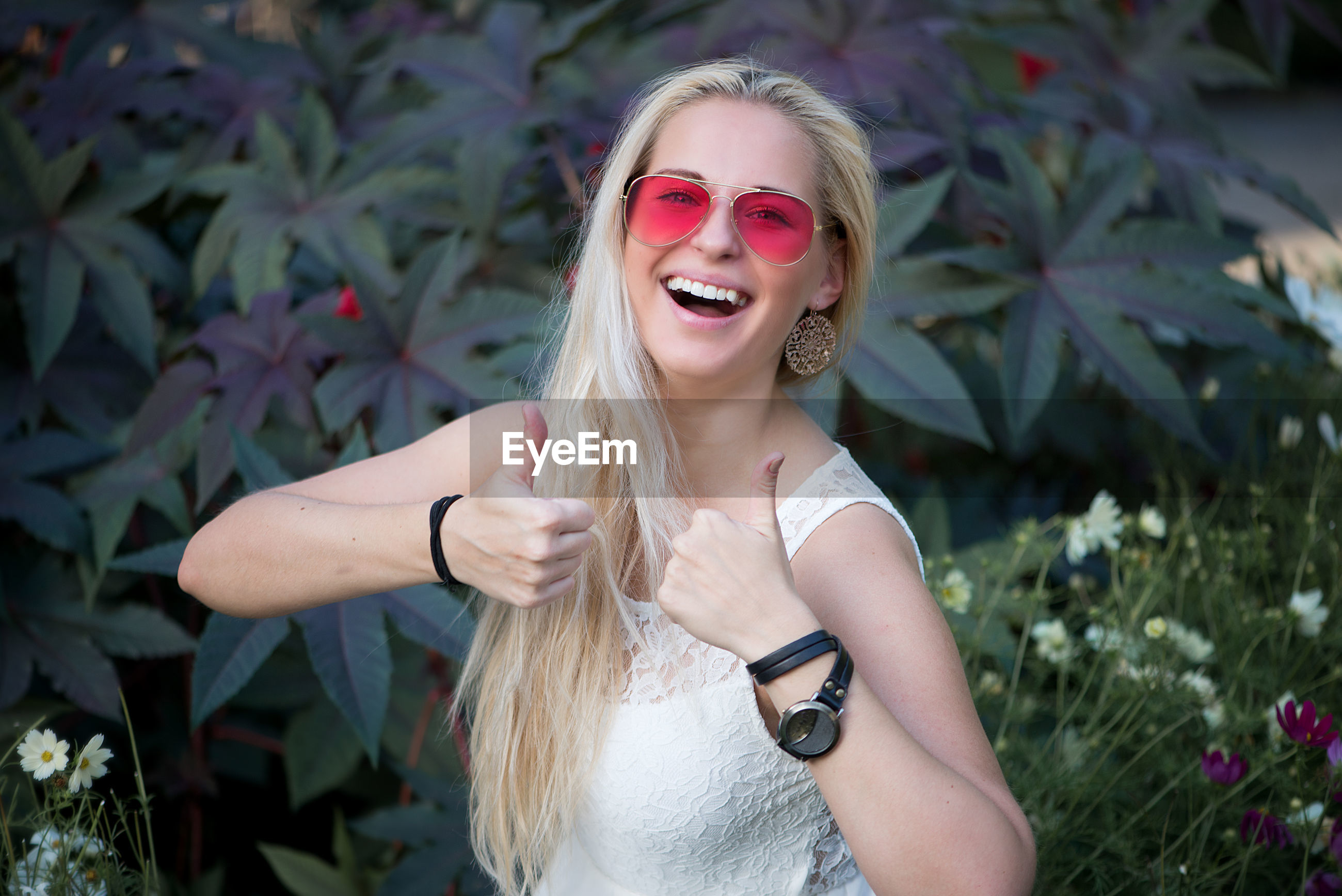 Portrait of beautiful woman gesturing thumbs up while standing against plants