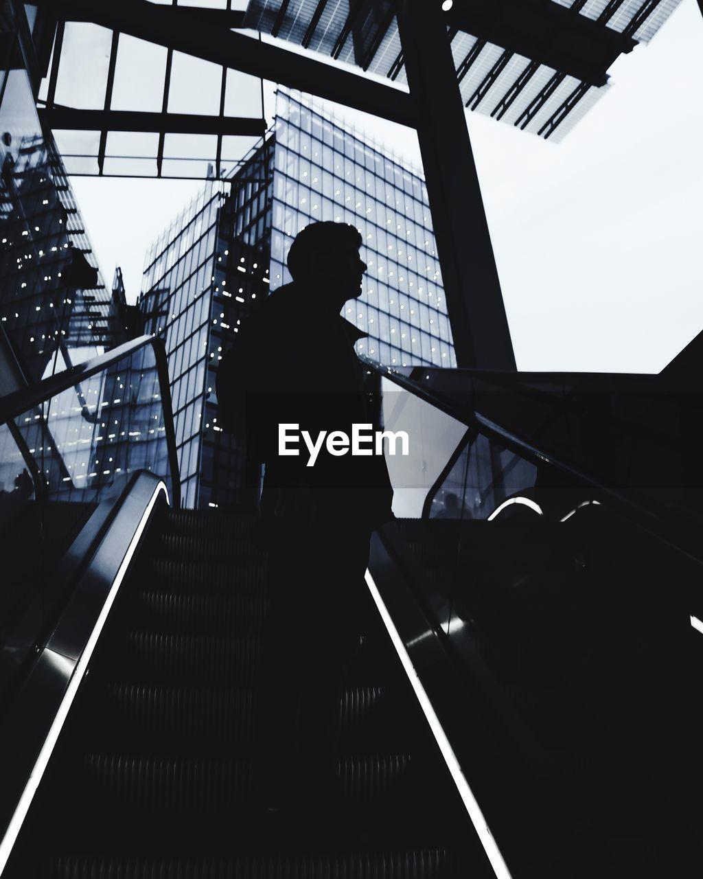 Silhouette Of Man Standing On Escalator