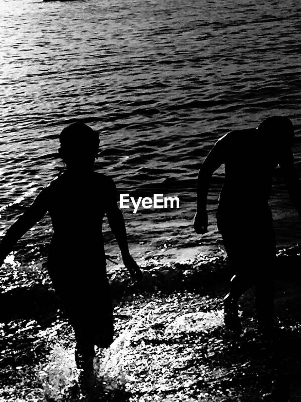 water, two people, real people, silhouette, togetherness, rear view, men, nature, lifestyles, outdoors, leisure activity, lake, bonding, women, beauty in nature, standing, day, scenics, ankle deep in water, people